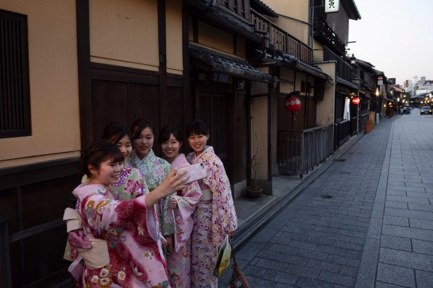 A group of Japanese women wearing kimono takes a selfie in the Gion district of Kyoto, Japan. Japanese tourism industry ...