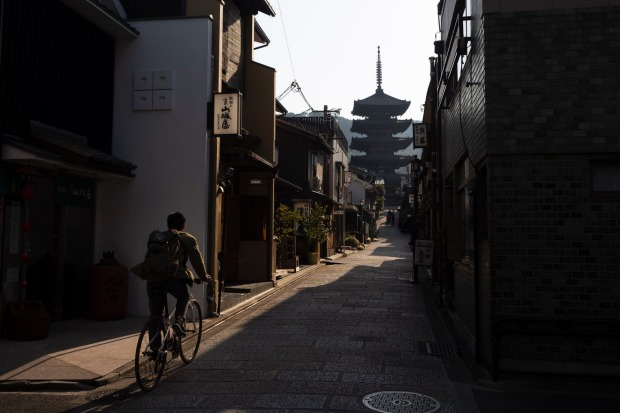 A man rides his bike toward Yasaka Pagoda in the Higashiyama district of Kyoto, Japan, March 19, 2020. Kyoto's city ...