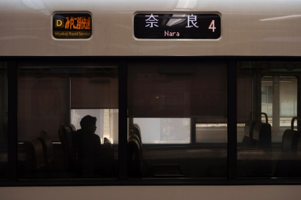 A man sitting in a train bound for Nara at Kyoto Station in Kyoto, Japan.