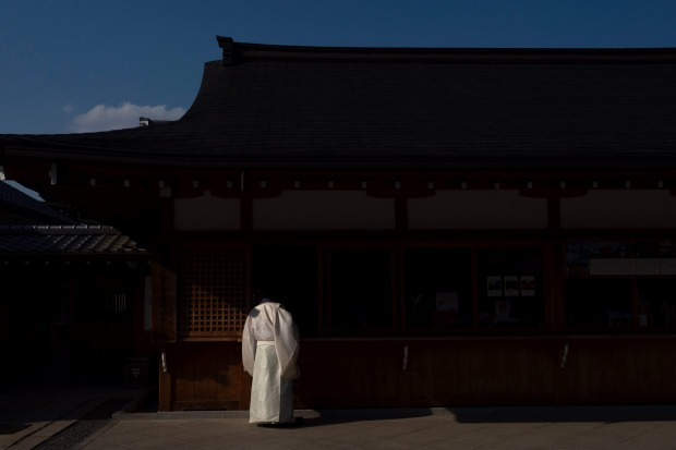 a Shinto priest talks to a a shrine maiden at Fushimi Inari Shrine in Kyoto, Japan. Japanese tourism industry has taken ...