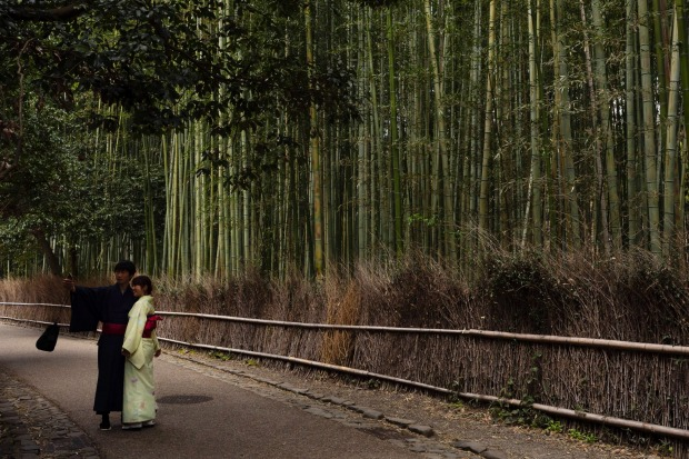 A couple takes a selfie at the Arashiyama Bamboo Forest in Kyoto, Japan, March 18, 2020. Widening travel restrictions ...