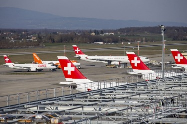 Swiss International Air Lines and easyJet planes are parked on the tarmac of the Geneve Aeroport in Geneva, Switzerland.