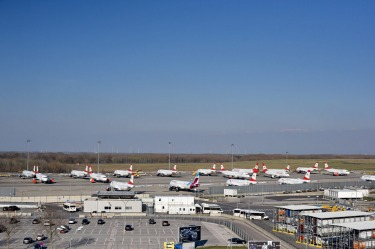 Austrian Airlines jets are parked at outside parking positions at Vienna International Airport.