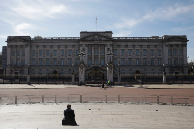 A lone person sits on the steps of the Queen Victoria Monument as looks at Buckingham Palace in London.