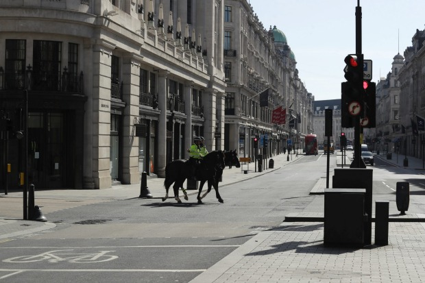 Two mounted police on a nearly deserted Regents Street in London.