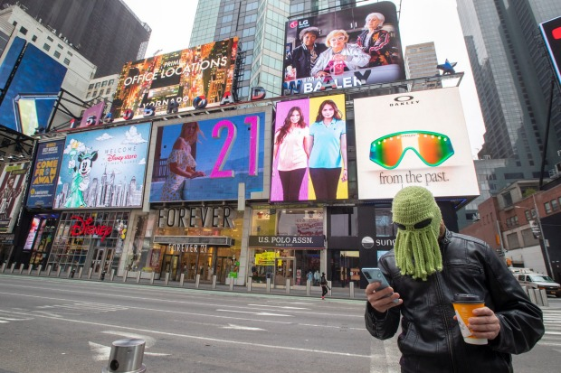 Jon Makay, of Harlem, wears an octopus hat to fend off coronavirus in New York's Times Square.