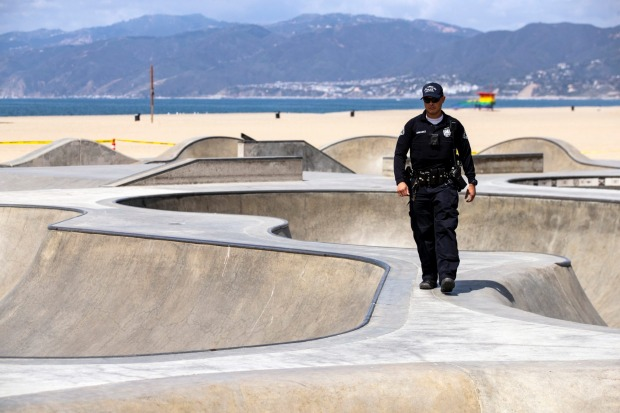 A LAPD officer patrols after asking people to leave the closed skatepark next to the beach amid the coronavirus pandemic ...
