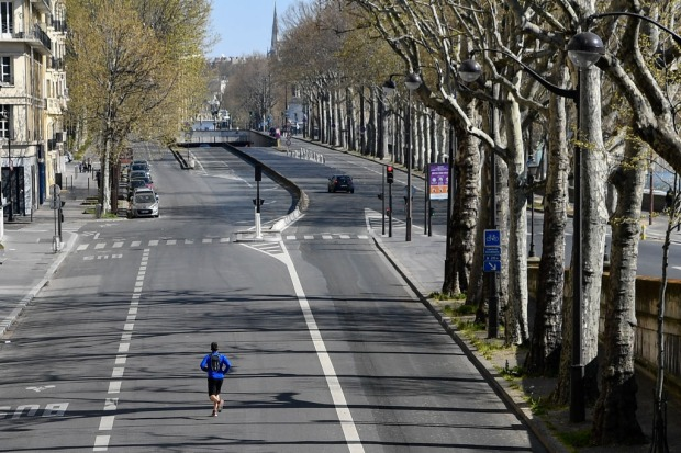A person runs in an empty street near the Eiffel Tower after preventive measures against the coronavirus (COVID-19) were ...