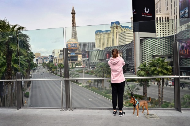 A woman with her dog photographs the nearly empty Las Vegas Strip after all the casinos and non-essential businesses in ...