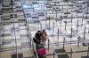 Travellers wearing face masks walk towards the taxi stand at the arrival hall of Changi Airport on March 23, 2020 in ...