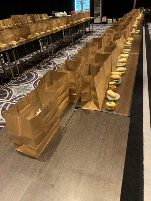 Bagged meals for the hotel's quarantined guests await their final items in the ballroom of the Sofitel Wentworth.