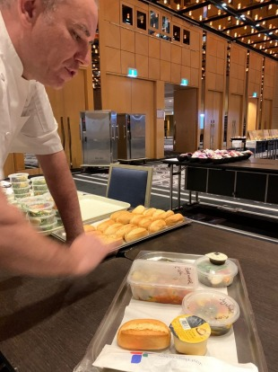 Boris Cuzon, the Sofitel Wentworth's executive chef, inspects one of the dinners prepared meals for quarantined guests ...