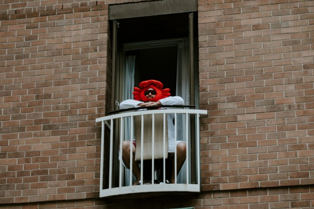 A quarantined guest enjoys the concert in the hotel's Garden Court from the vantage point of his balcony.
