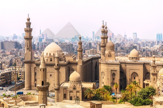 The Mosque-Madrassa of Sultan Hassan and the Pyramids in the background of bustling, Cairo, Egypt.  The Egyptian ...