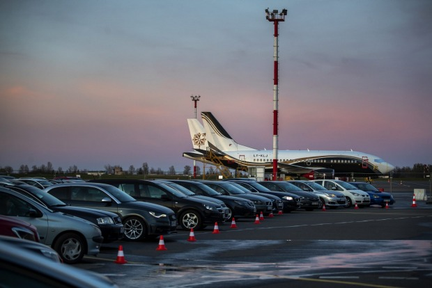 People sit in their cars watching a movie at a new drive-in cinema on a airport apron area, where the planes take off ...