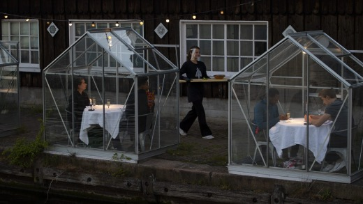 Staff at the Mediamatic restaurant serve food to volunteers seated in small glasshouses during a try-out of a setup ...