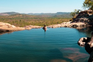A woman looking out from the Gunlom plunge pool.<br /><br />Covering nearly 20,000 square kilometres, Kakadu ...