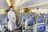 Emirates cabin crew wear personal protective equipment on flights to guard against COVID-19. Australians are in limbo ...