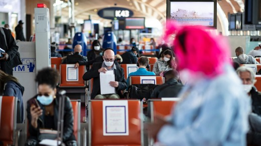 Passengers wearing face masks await their departure in Terminal 2 of Charles de Gaulle international airport.