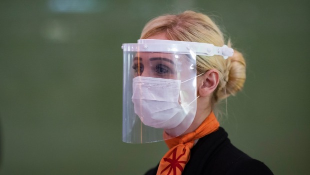 A member of Charles de Gaulle airport personnel wears a protective face mask and a visor in Terminal 2 of Charles de ...