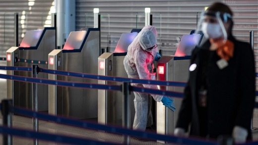 A personnel member cleans a gate as another member of Charles de Gaulle airport personnel wears a protective face mask ...