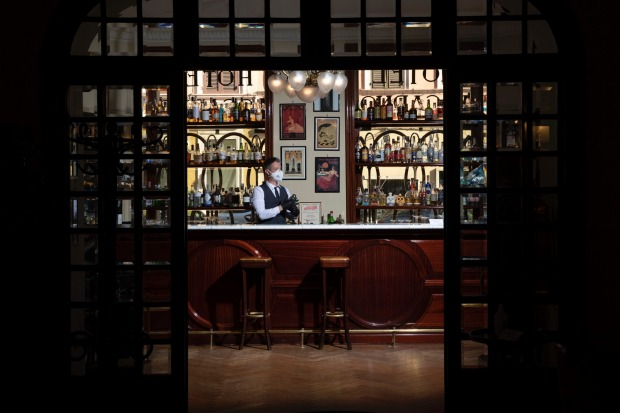 Barman Nicholas Pinna wears a protective face mask as he stands behind the cocktail bar of the art-deco style Locarno ...