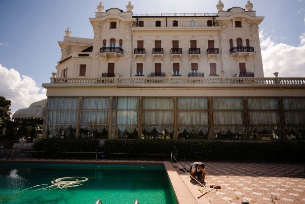 A man does maintenance work by a swimming pool of the Rimini Grand Hotel, in Rimini, Italy. The luxury Liberty-style ...