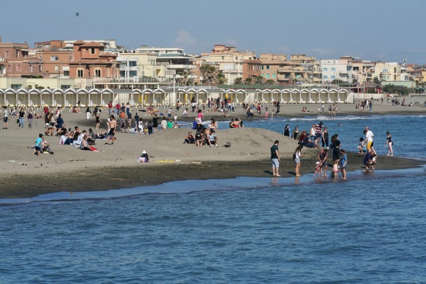 People enjoy the warm weather as they gather at Ostia beach, near Rome. Europeans and Americans soaked up the sun where ...