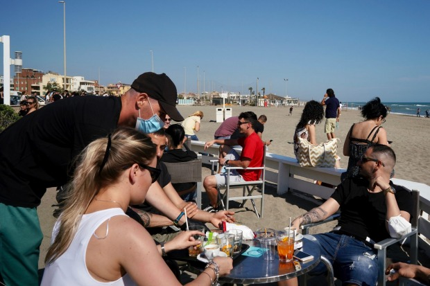 People sit at an outdoor cafe in Ostia beach, near Rome.