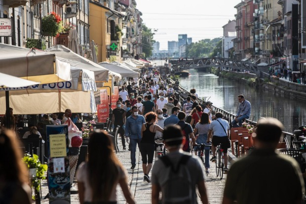 People take a walk and relax at the Naviglio Grande canal, in Milan, Italy. Europeans and Americans soaked up the sun ...