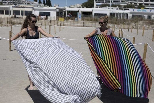 Beach goers set down their towels in an area marked to enforce social distancing measures in La Grande Motte, southern ...