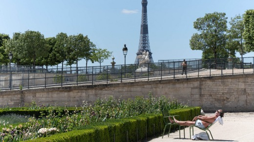 People sunbathe at the Jardin des Tuileries with the Eiffel Tower in the background.