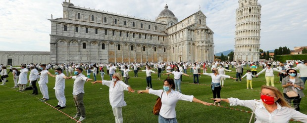 People gather for a flash mob on the Miracle's square to celebrate the reopening of the Leaning Tower.