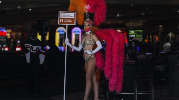 A showgirl wearing a protective mask promotes social distancing at the entrance to the Flamingo Las Vegas casino