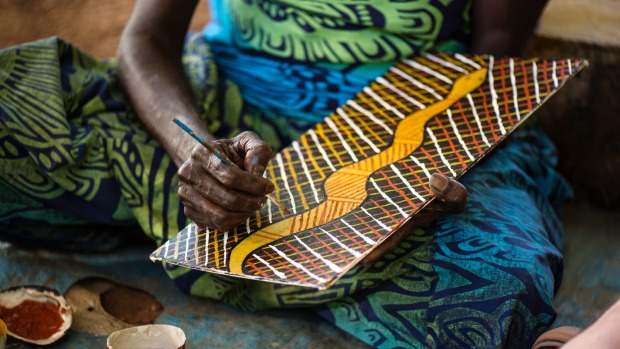 An artist painting at Tiwi Design