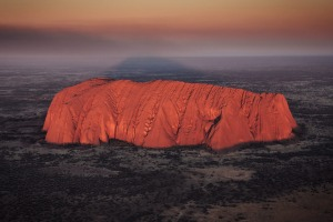 Uluru glowing at sunrise during a helicopter tour. One of the great natural wonders of the world, Uluru towers above the ...