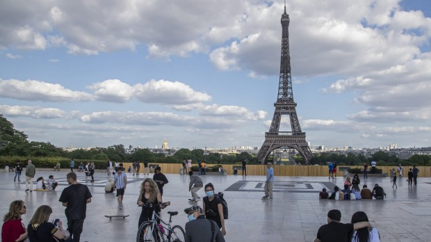 People stroll around Trocadero Square near the Eiffel Tower as lockdown restrictions lift.