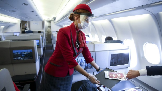 A flight attendant wears both a face mask and shield.
