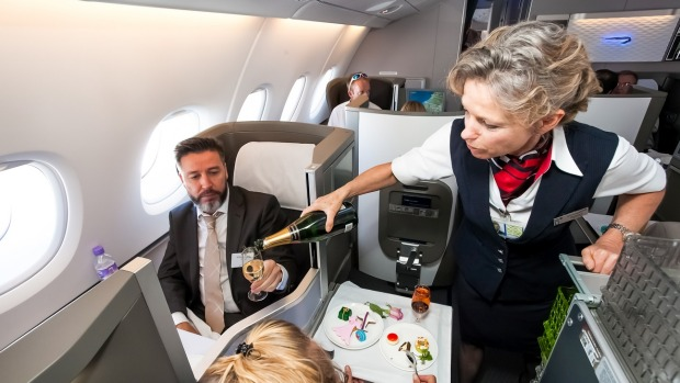 A passenger is served champagne in business class.