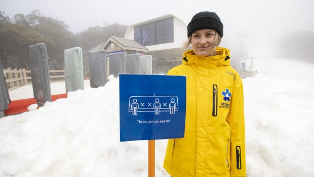 Mt Buller staff member Kate Moffatt displays the social distancing measures the resort will use on their ski lifts.
