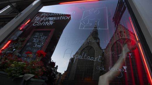Oude Kerk, or Old Church, is reflected in the window of the Prostitution Information Centre as sex workers welcomed ...