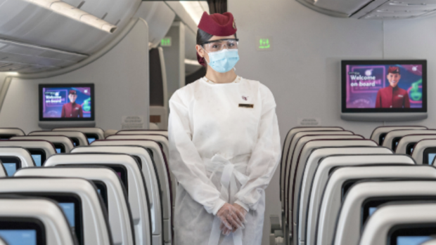 A cabin crew member wears the shield and mask, in addition to a new protective gown.