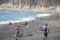 Tourists are seen relaxing, sunbathing and swimming at Vlichada Beach in Santorini.