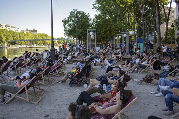 """People attend the """"Le Cinema Sur L'Eau"""", or Cinema on the Water, organised by Paris Plages."""