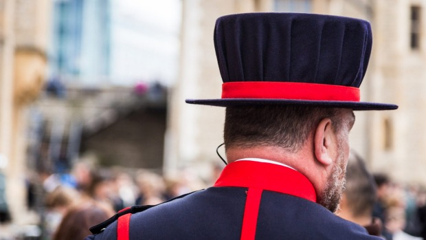 A Yeoman Warden or 'Beefeater' conducts a public tour of the Tower of London.