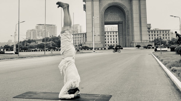 Joachim Bergstrom does a handstand in front of a North Korean landmark.