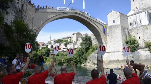 Divers wait to jump from Mostar bridge during 454th traditional diving competition.