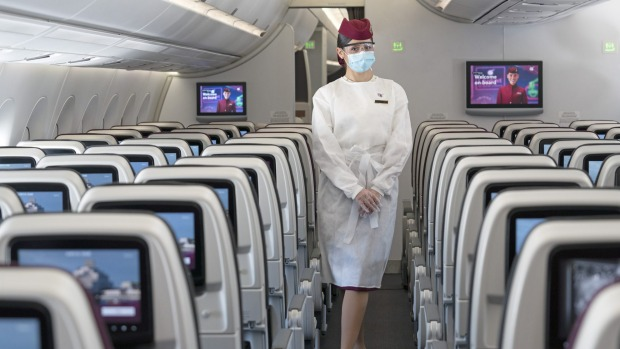 A Qatar Airways flight attendant wearing her personal protective equipment (PPE).