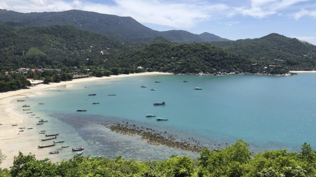 Fishing vessels and boats used to ferry tourists sit idle along a deserted beach on the popular tourist island of Koh ...