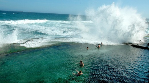 Swimmers watch as waves crash over Bogey Hole.